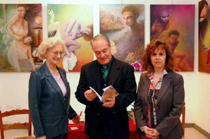 Roma, Galleria La Pigna - L'Ing. Corduas, direttore Artistico di Napoli Nostra prende visione del libro di Aurora Mazzoldi (a sin.) che sarà presentato al pubblico nel corso della mostra. A destra la psicologa-psicoterapeuta introspettiva Antonella Giannini. Sullo sfondo quadri di Aurora Mazzoldi